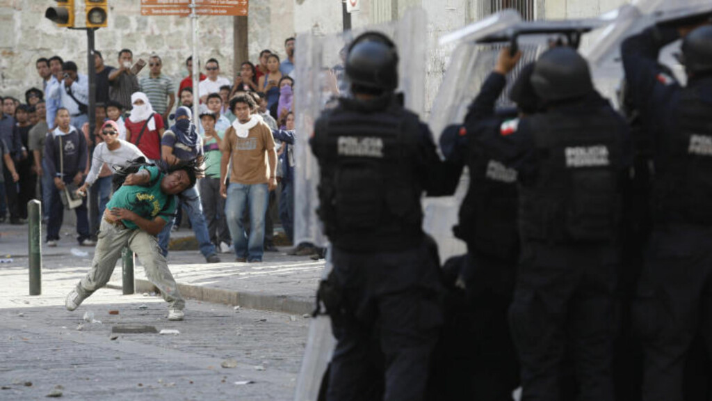 KASTET STEINER: Lærerne kastet steiner og slo politifolk med stenger, mens politiet skjøt tilbake tåregass. Foto: Reuters/Jorge Luis Plata/Scanpix