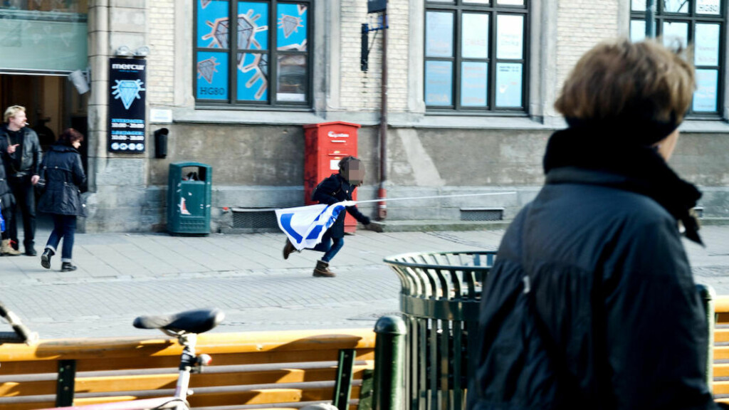 - STJELER FLAGGET: Her løper en kvinne avgårde med flagget til Med Israel (Miff) for fred i Trondheim sentrum. Foto: Roy-Cato Myrvang