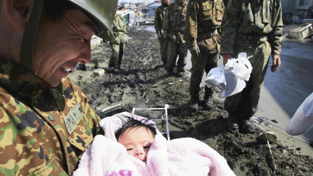 I TRYGGHET: En fire måneder gamle jenta ligger her trygt i armene til den japanske soldaten. Jenta ble reddet ut av ruinene i Ishimaki nord i Japan - tre dager etter jordskjelvet som la store deler av regionen i ruiner. Foto: Hiroto Sekiguchi/Ap