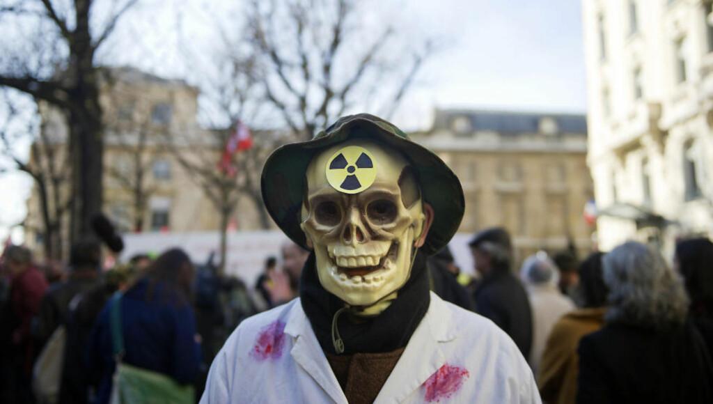 PROTESTERER: Etter atomulykken i Japan har mange demonstrert mot bruken av kjernekraft, som denne mannen i Paris. Men thorium kan være et alternativt reaktorbrennstoff. Norge kan bidra ved å støtte nødvendig forskning og utnytte thorium fra Fensfeltet, skriver kronikkforfatteren. Foto: Scanpix