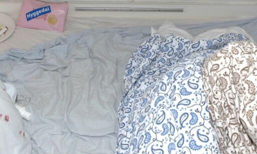 image: På et dolokk sitter en politibetjent. I badstua sitter Andrea. I en campingvogn sover tre menn