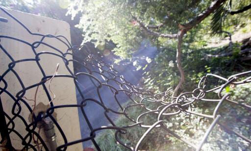 Bildet viser et delvis ødelagt gjerde, utenfor tomta til Miranda Kerr i Malibu i California. Foto: Splash News/NTB Scanpix