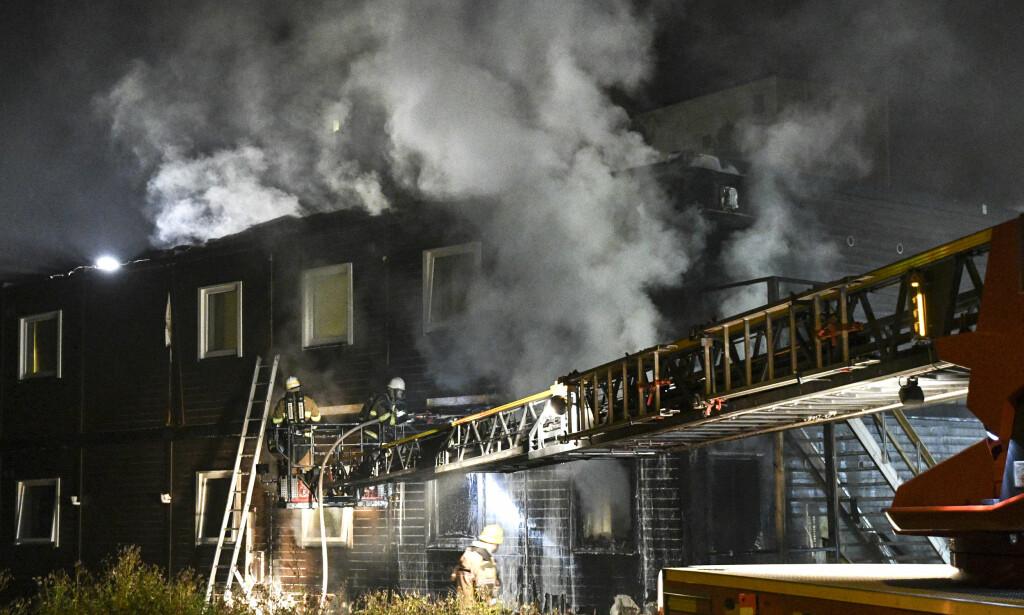 KRAFTIG BRANN: Brannvesenet jobber natt til søndag med å slukke en brann i et asylmottak i Fagersjö, sør i Stockholm. Foto: Johan Nilsson / TT / NTB Scanpix