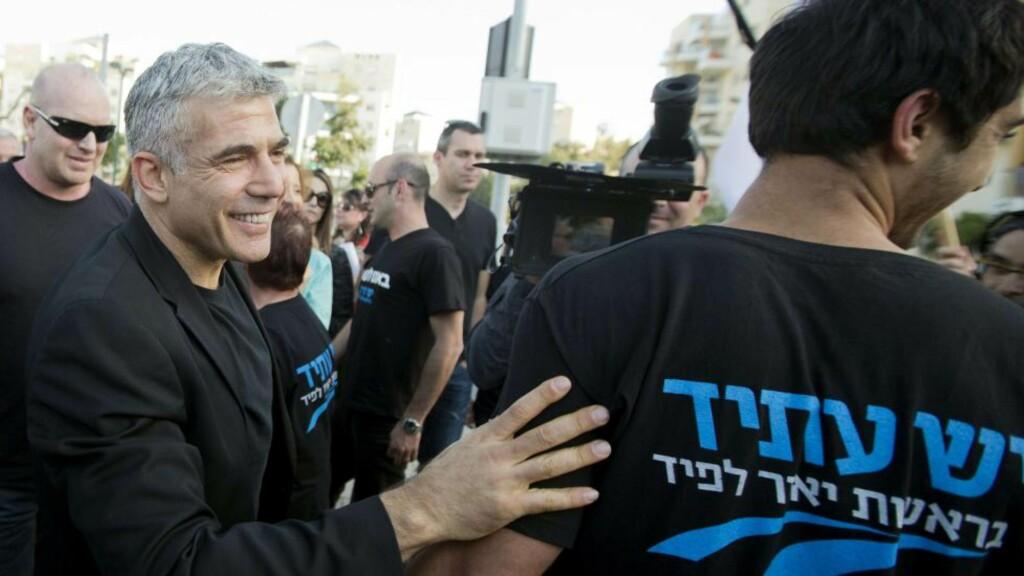NOK EN ROLLE: Den israelske skuespilleren, journalisten og forfatteren Yair Lapid (t.v), leder det nye Yesh Atid-partiet i Israel, som har gjort et brakvalg. Her besøkte han et valglokale i kystbyen Netanya i går. Foto: Jack Guez/Afp/Scanpix