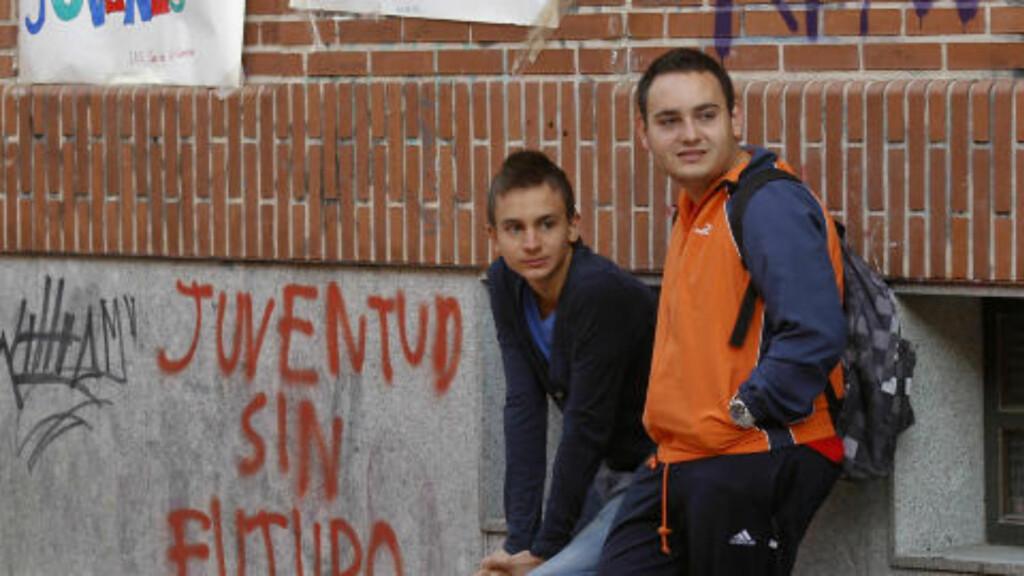 STUDERER, MEN TIL HVA? To spanske studenter i Madrid står og venter på at dagens arbeidsdag skal starte. Men sjansen for at disse to - og Spanias unge befolkning får jobb, blir stadig mindre. Nå er hele 60 prosent av Spanias unge under 25 år uten jobb. Foto: Andrea Comas/Reuters/Scanpix
