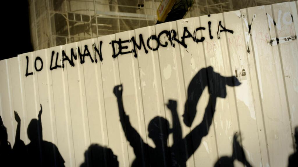 """UNGDOM UTEN FRAMTID:  Skyggene av unge demonstranter vises på et gjerde i Madrid, der en gruppe som kaller seg """"Ungdom uten en framtid"""" protesterer mot at Spanias ungdom ikke kommer seg inn på arbeidsmarkedet. Spanias arbeidsløshet for ungdom under 25 år er nå på hele 60 prosent, som er verst i Europa. Foto: Pedro Armestre/Afp/Scanpix"""