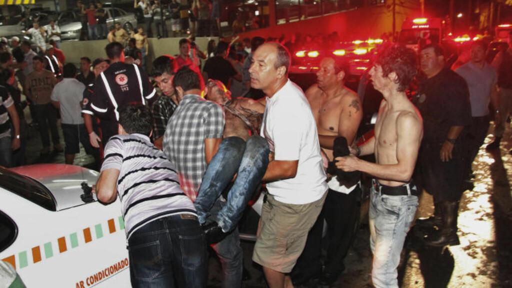 KAOS:  En skadet person blir båret ut av nattklubben, som skal ha startet i 02.00-tida lokal tid. Foto: AP Photo/Deivid Dutra