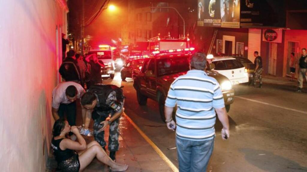 - PANIKK:  En kvinne får vann av politiet, etter å ha kommet seg ut på fortauet. Ifølge flere medier skal det ha oppstått panikk da brannen brøt ut på nattklubben. Foto:  AFP PHOTO / AGENCIA RBS / LAURO ALVES