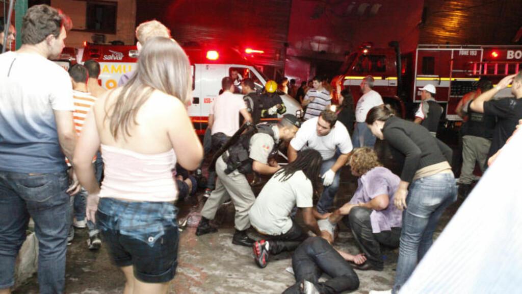 MINST 245 OMKOM:  Hardt skadede personer ble tatt hånd om av helsepersonell på plassen utenfor nattklubben med navn Kiss. Foto: REUTERS/Germano Roratto/Agencia