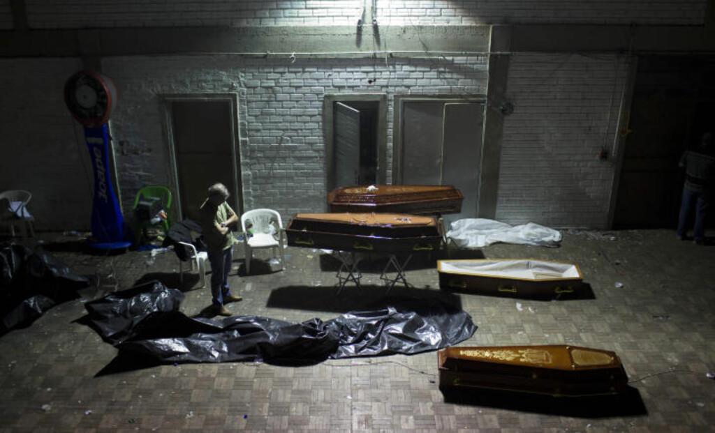 PROVISORISK LIKHUS: En gymsal brukes for å oppbevare kister med ofre fra brannen. Foto: FELIPE DANA / AP / NTB SCANPIX