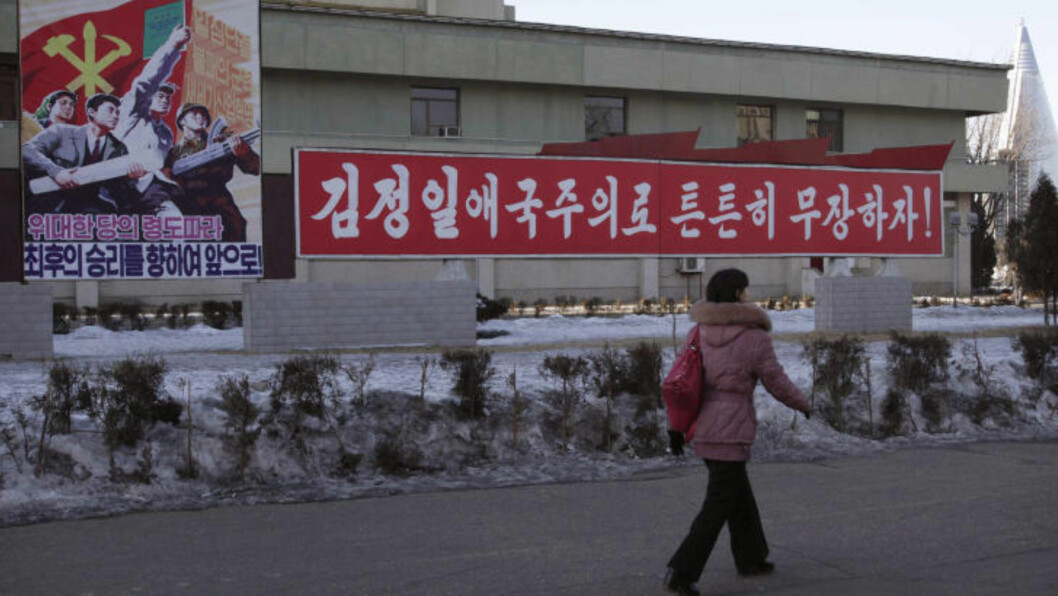 """A woman walks by a board which reads """"Forward to Final Victory under Leadership of Great Party,  left, and another reads reads """"Let's firmly arm ourselves with the patriotism of Kim Jong Il,"""" in Changgwang Street, Pothonggang District of Pyongyang, North Korea, Friday Jan, 25, 2013. Following new U.N. sanctions punishing North Korea for a December rocket launch, North Korea warned that it would continue launching long-range rockets and conduct a nuclear test. (AP Photo/Kim Kwang Hyon)"""