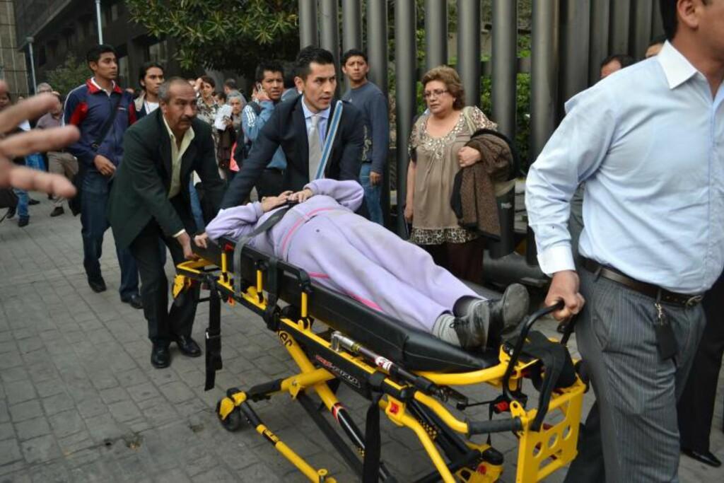 HJELPER KOLLEGA: Pemex-ansatte hjelper en skadd kollega etter eksplosjonen. Foto: AFP / NTB SCANPIX