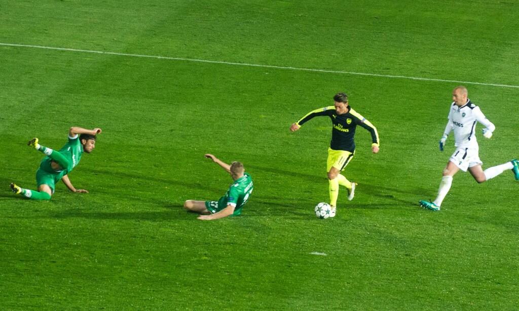 LEKTE SEG: To forsvarspillere ligger og spreller. Keeperen forsøker desperat å nå igjen Özil. Men den tyske eleganten lar seg ikke stoppe. Foto: NTB Scanpix