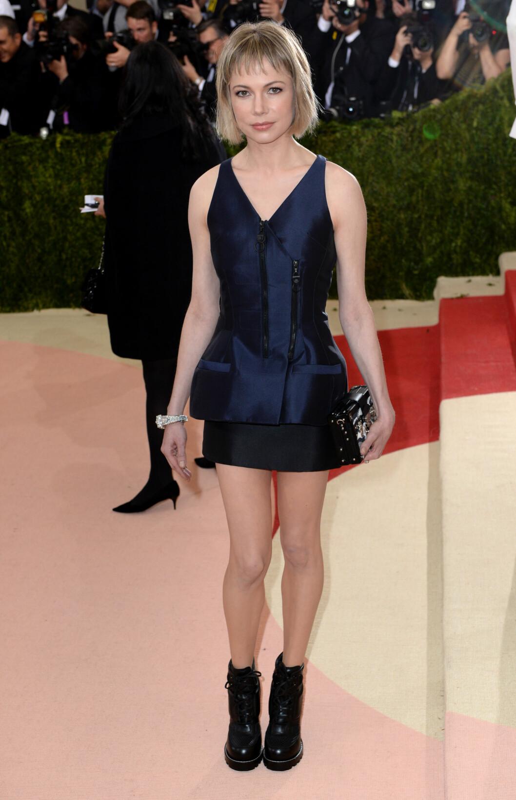 FOR ENKELT: Skuespiller Michelle Williams imponerte ikke i denne midnattsblå minikjolen med glidelåsdetalj, stylet med sorte boots og boksclutch. Foto: Pa Photos