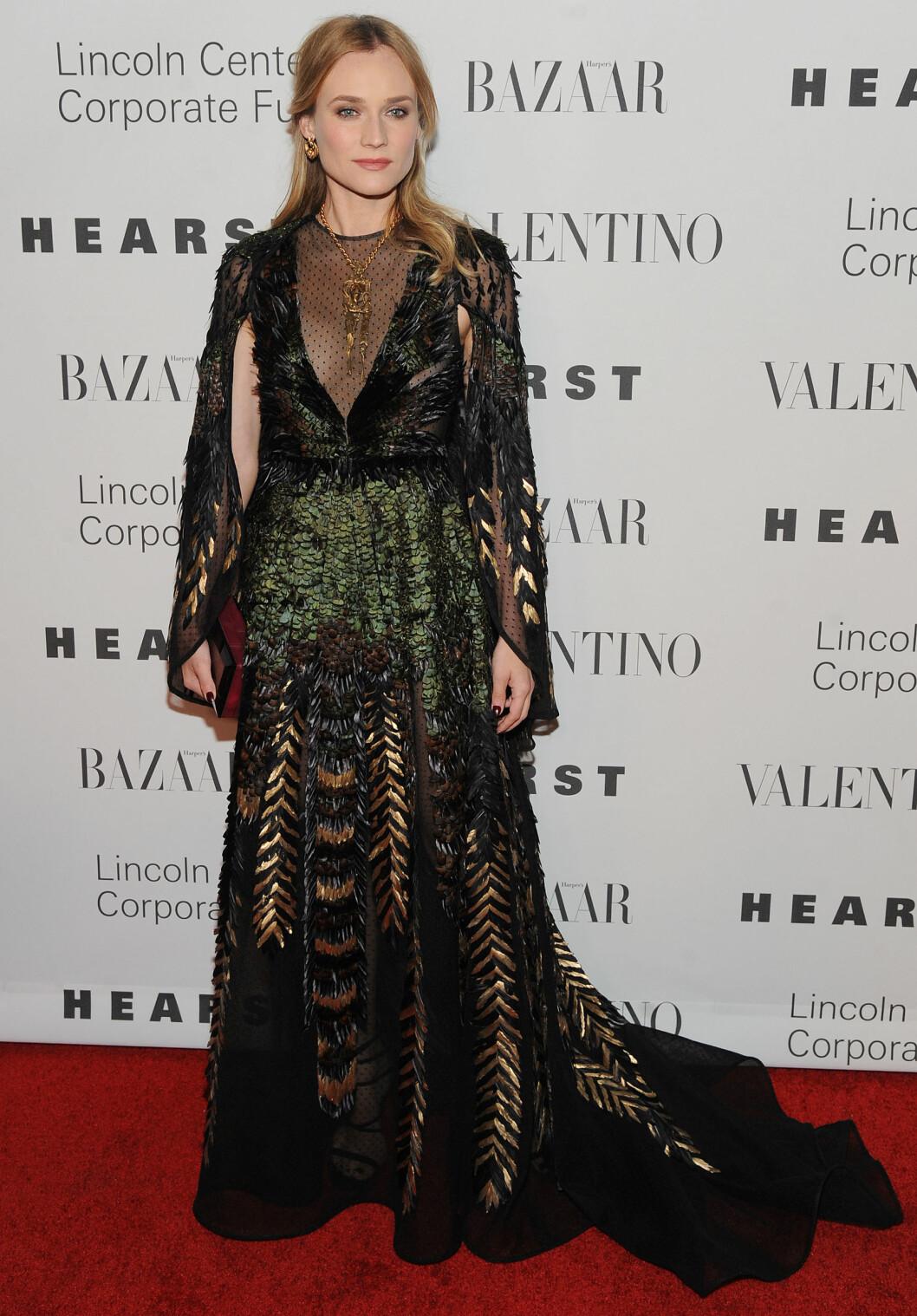 <strong>VAKKER PÅFUGL:</strong> Skuespiller Diane Kruger får skryt for sin vakkert broderte fjærkjole fra Valentions couture-kolleksjon for høsten 2015. Det massive gullsmykker gjorde kjolens utringning mer «kledd». Foto: Broadimage