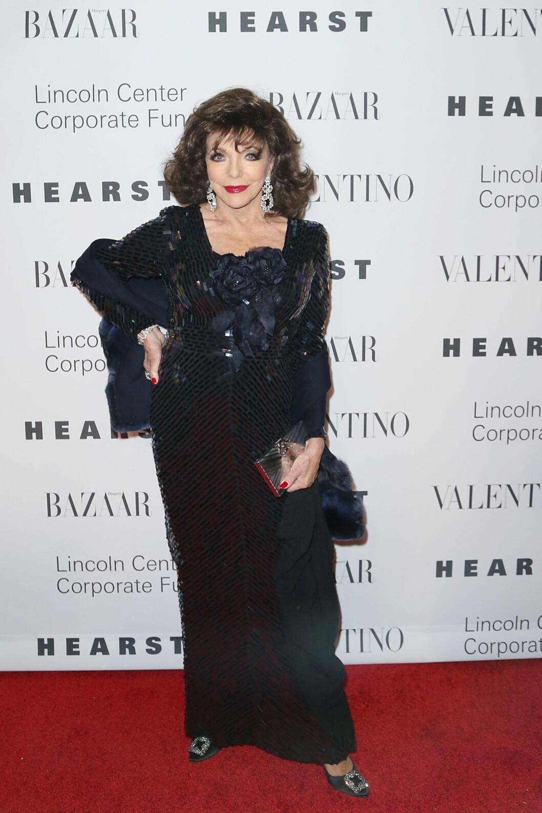 <strong>FULL GLAMOUR:</strong> Skuespillerdiva Joan Collins strålte i en paljettbesatt, midnattsblå kjole stylet med røde lepper og negler, glitrende sko og øredobber, samt en boksclutch i sølv.  Foto: SipaUSA