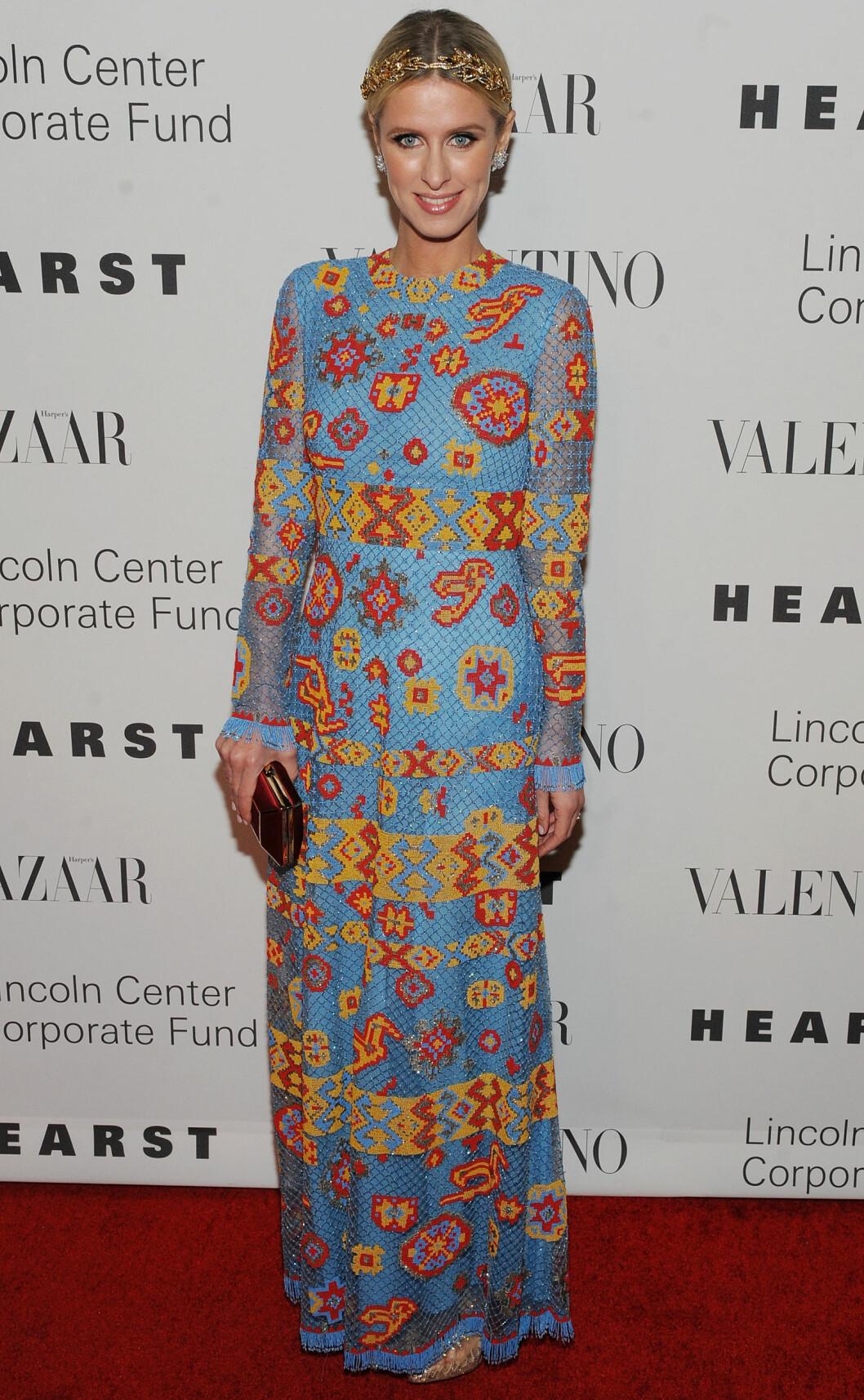 <strong>FARGESPRAKENDE:</strong> Hotellarving Nicky Hilton overrasket i en fargerik kjole fra Valentinos kommende vårkolleksjon. Hun stylet kjolen med store øredobber, hårbånd i gull og en matchende clutchveske.  Foto: Broadimage