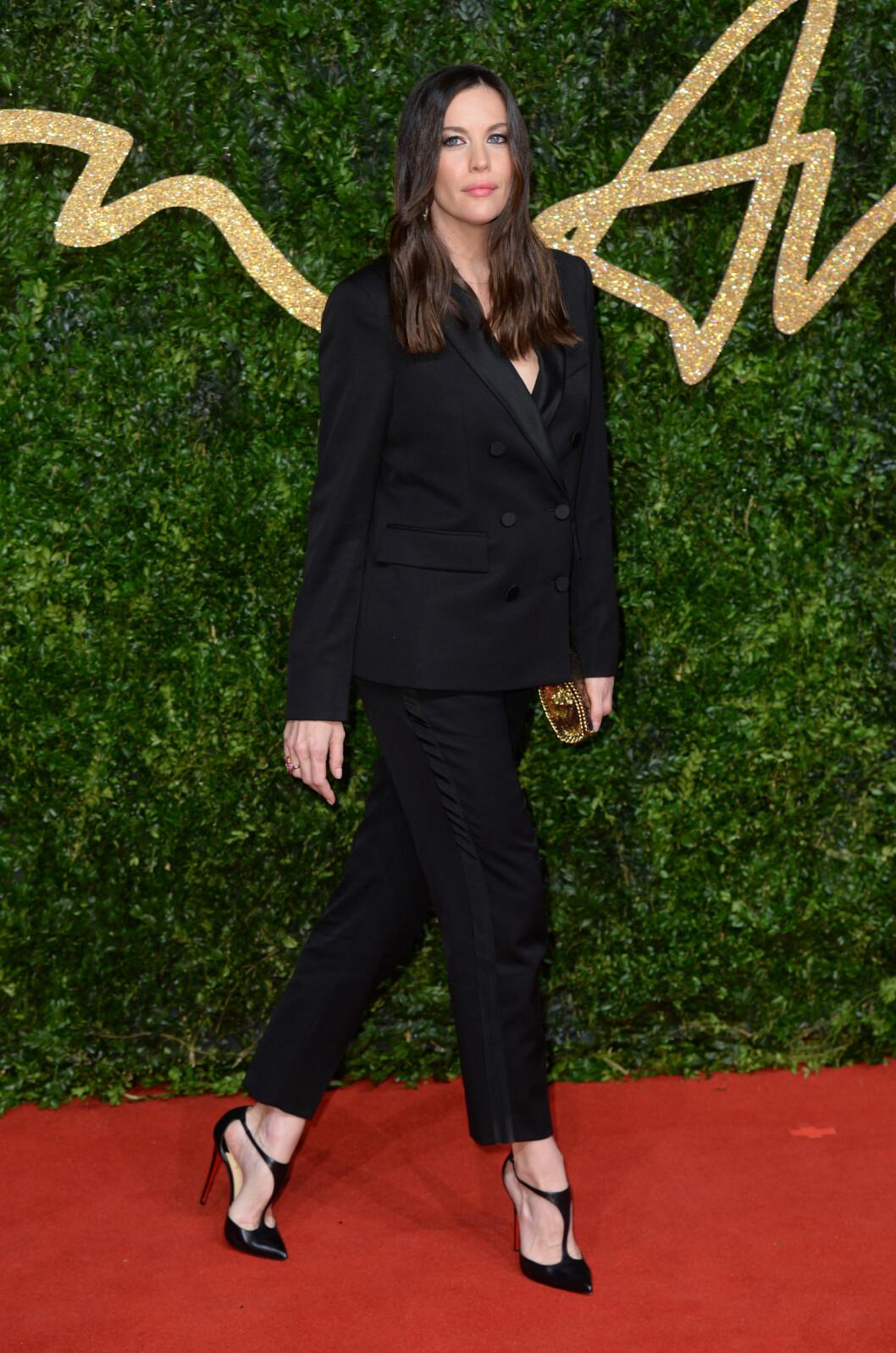 <strong>MATCHET VICTORIA:</strong> Liv Tyler valgte en dobbeltspent, sort dress til årets British Fashion Awards. De sexy skoene og den glitrende vesken gjorde antrekket mer lekent.   Foto: Pa Photos