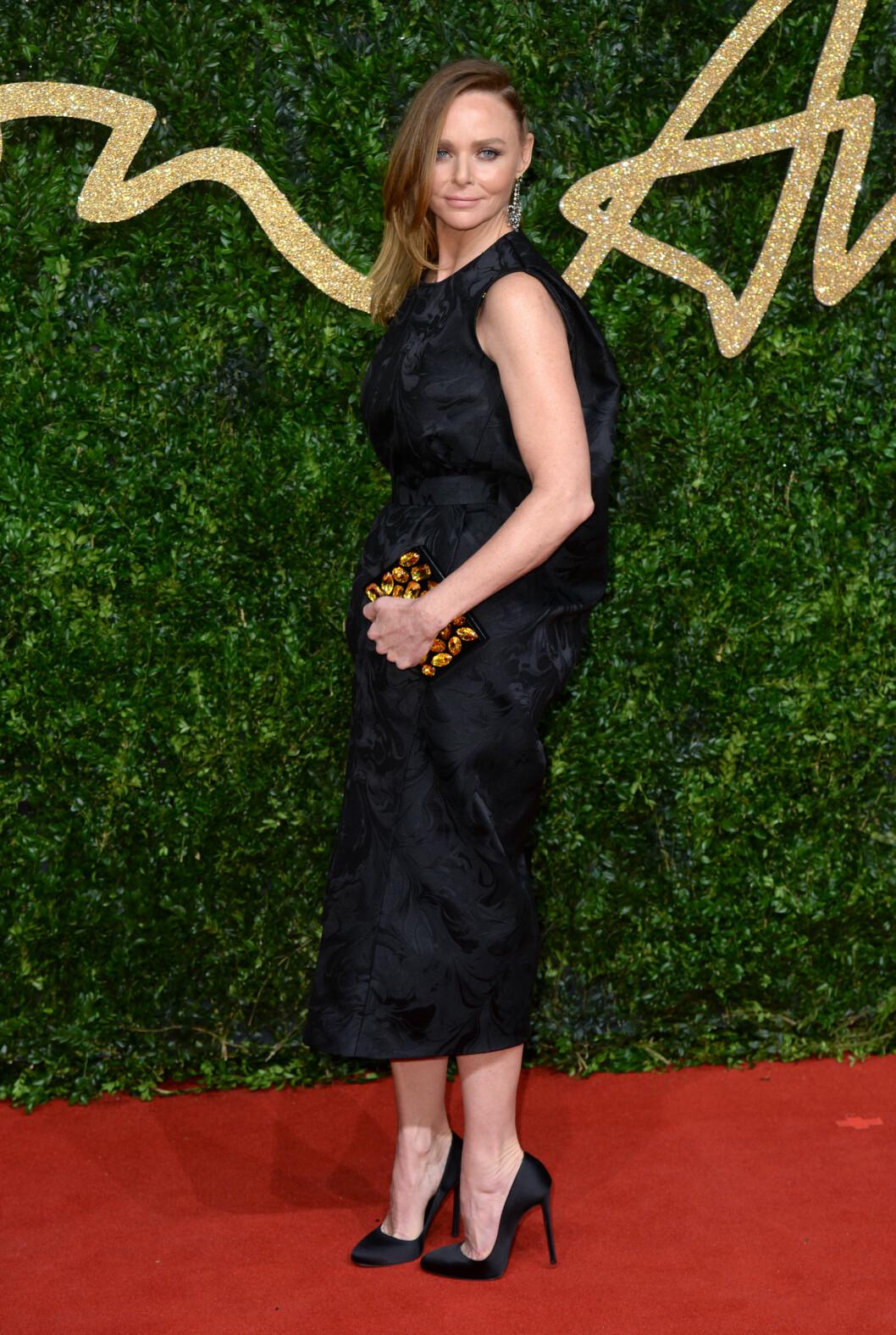 <strong>DRAMATISK:</strong> Designer Stella McCartney valgte en sort kjole med draperinger og diskret mønster, stylet med matchende pumps og glitrende clutchveske. Foto: Pa Photos