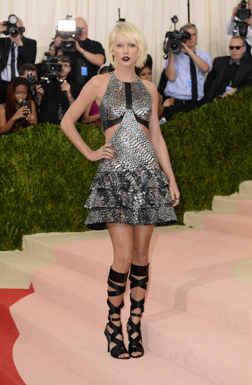 LÅRKORT: Popstjerne og Met Gala-vertinne Taylor Swift ovverasket i en metallisk minikjole med slangeprint, stylet med høye stroppesandaler.  Foto: Pa Photos