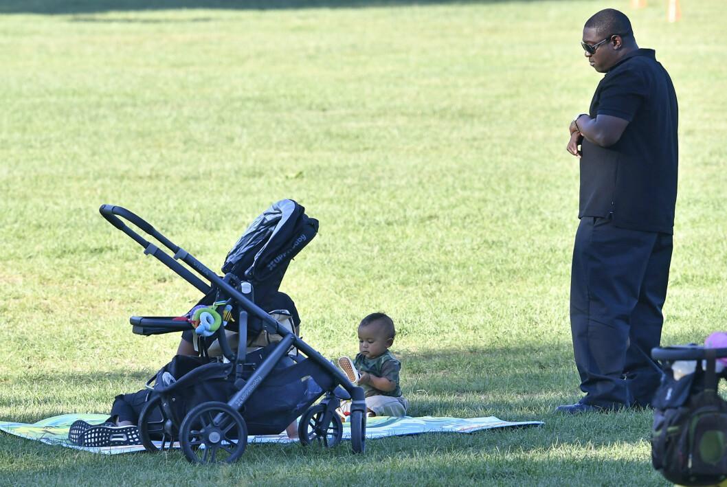 STJERNEBABY: Det var unektelig et litt pussig syn da den mørkkledde livvakten stod rolig og så på Saint West mens han lekte i Central Park.  Foto: Splash News