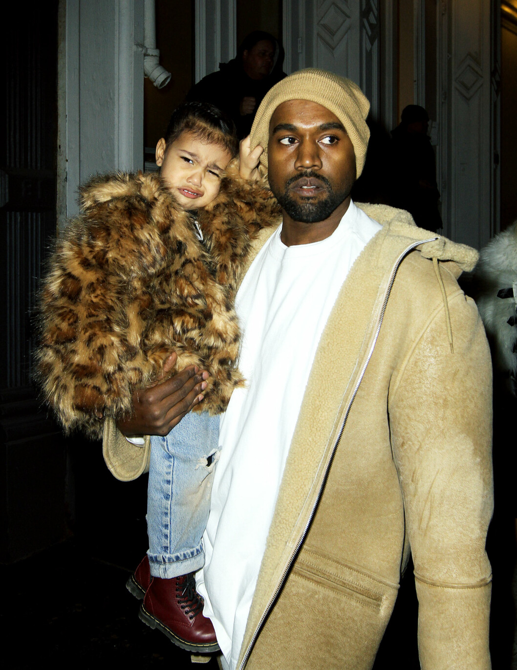 IKKE HELT BLID: Kanye West avbildet med datteren North på armen ute i New York i februar. Paret er blitt kritisert for å drive datteren sin for hardt.  Foto: Splash News