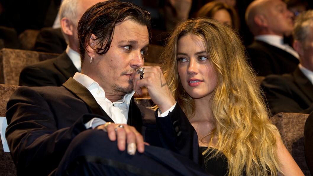 VOLDSOMT TEMPERAMENT: Amber Hear hevder at Johnny Depp kvestet sin egen finger under et raserianfall i mars i fjor, før han malte utroskapsanklager mot henne i blod og maling på veggen. Her er paret avbildet sammen på «Black Mass»-premieren under filmfestivalen i Venezia i september 2015. Hvorfor Depps langfinger var plastret da, vites ikke. Foto: DPA