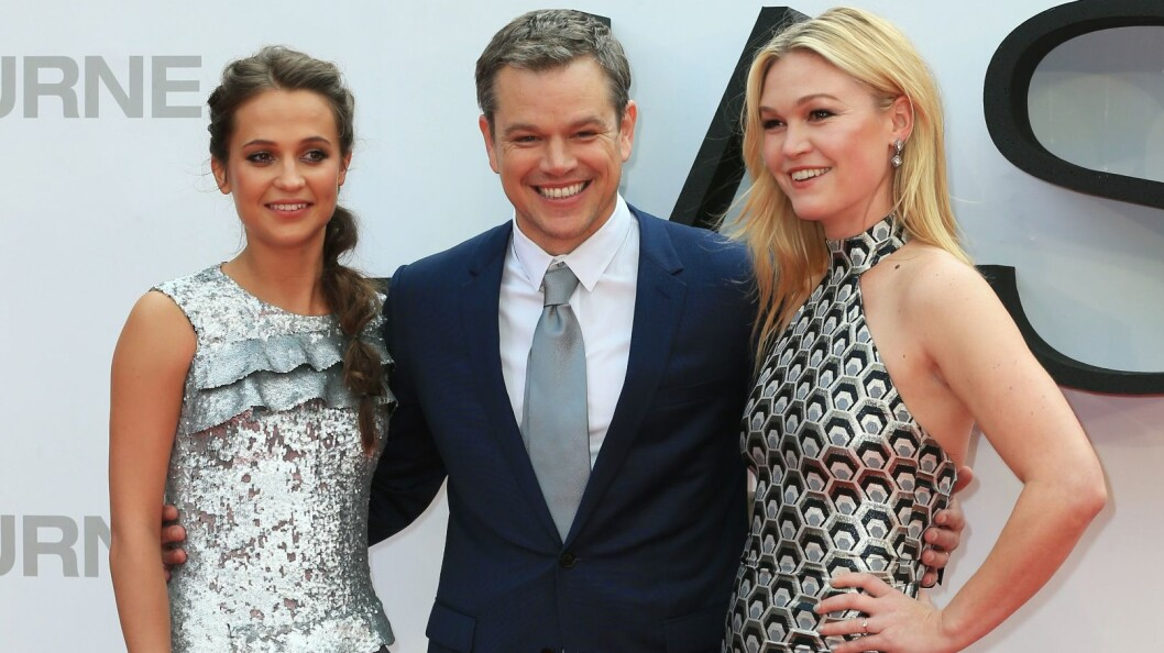 SMILTE BREDT: Matt Damon smilte så godt han kunne, men det var hans kolleger Alicia Vikander (t.v.) og Julia Stiles som fikk flest blikk under premieren på den nye «Jason Bourne»-filmen i London mandag. Foto: Rex Features