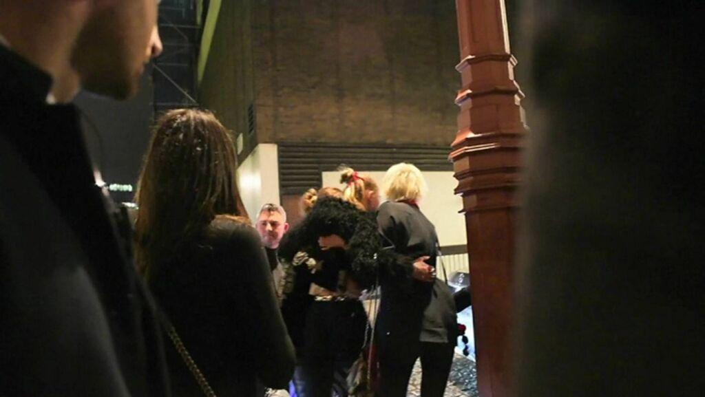 FIKK HJELP: Den blonde supermodellen fikk god hjelp av ei som kan se ut som en god venninne av henne.  Foto: NTB scanpix