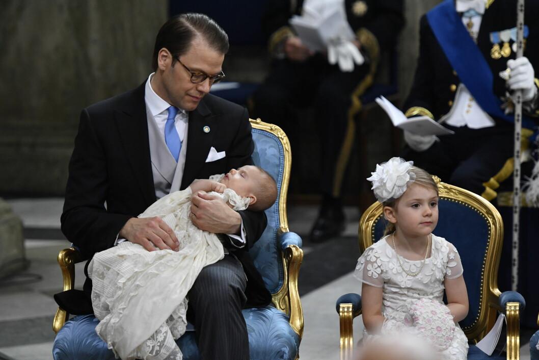 <strong>SJARMTROLL:</strong> Lille prins Oscar sov godt på pappas fang under dåpsseremonien.  Foto: TT NYHETSBYRÅN