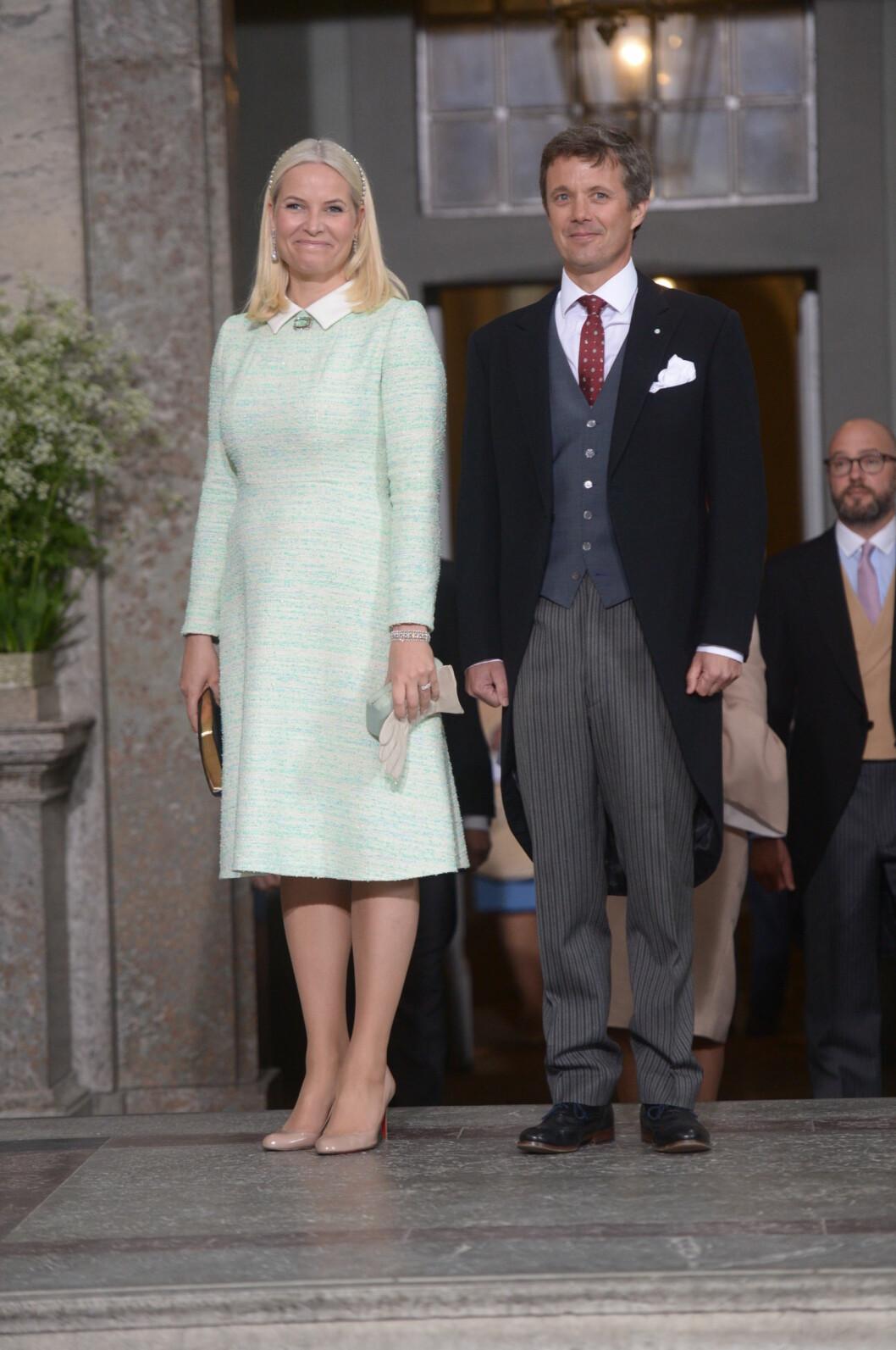 <strong>STRÅLTE I GRØNT:</strong> Kronprinsesse Mette-Marit ankom sammen med kronprins Frederik av Danmark. De er begge faddere til prins Oscar.  Foto: TT NYHETSBYRÅN