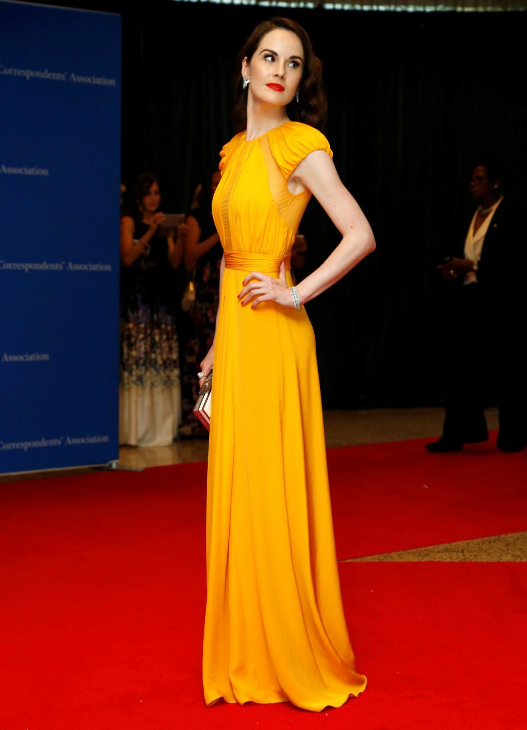 VAKKER: Skuespiller Michelle Dockery poserte foran presseveggen ikledd en lang gul kjole med Hollywood-krøller og klassiske røde lepper.  Foto: Reuters