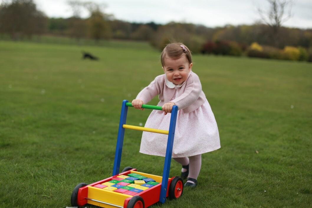 PYNTET MED SLØYFE I HÅRET: På bildene har lille Charlotte på seg et helrosa antrekk og en søt sløyfe i håret. Hun smiler bredt mens hun leker ute i hagen.  Foto: Epa