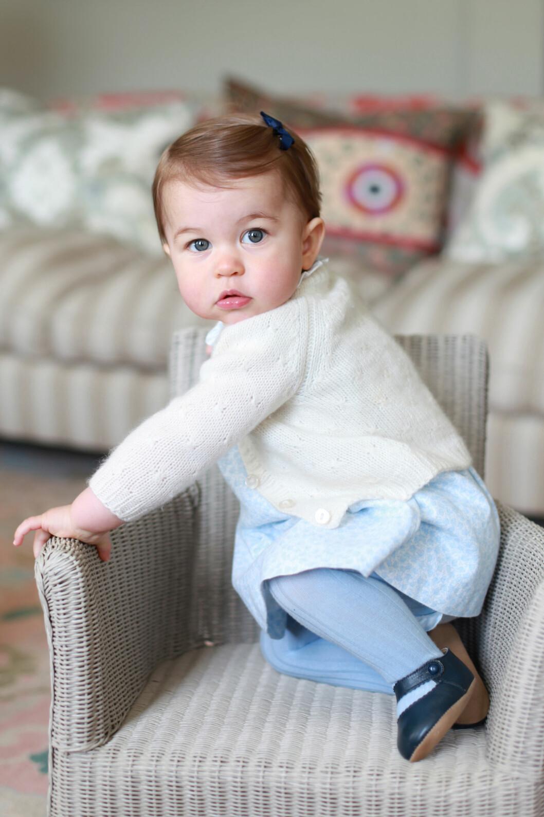 SJARMERER I SENK: På et av bildene er prinsesse Charlotte ikledd en blå kjole, med blå sløyfe i håret. I tillegg har hun på seg en kremhvit strikkejakke.  Foto: Reuters