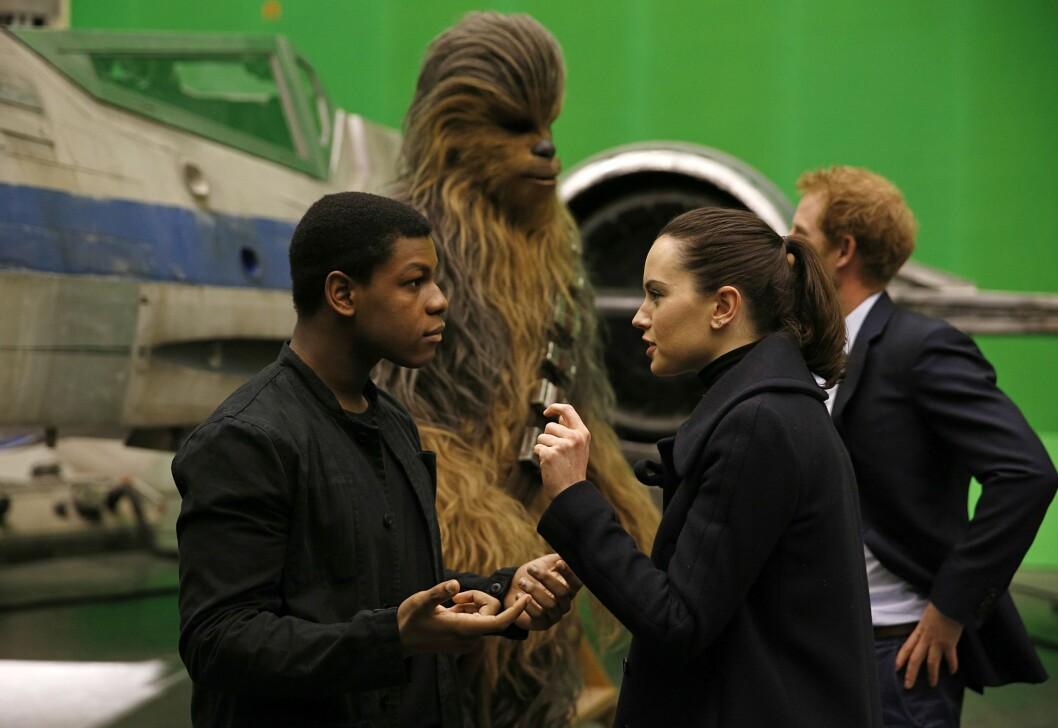 STJERNEMØTE: De unge «Star Wars»-stjernene John Boyega og Daisy Ridley (foran) prater mens prins Harry står i ivrig samtale med Chewbacca. Foto: Pa Photos