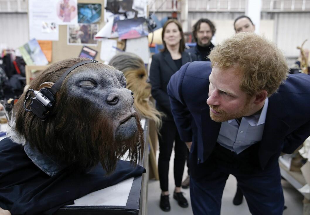 AVANSERTE FILMTRIKS: Prins Harry studerer en robotstyrt maske fascinert under omvisningen i Pinewood Studios tirsdag. Foto: Pa Photos
