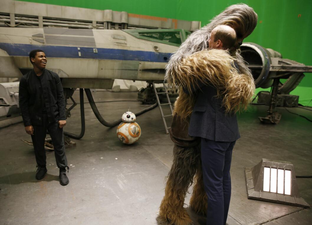 FIKK OGSÅ KLEM: Chewbacca forbarmet seg også over prins William under besøket. Den britiske skuespilleren John Boyega (t.v) fulgte lattermildt med!  Foto: Reuters