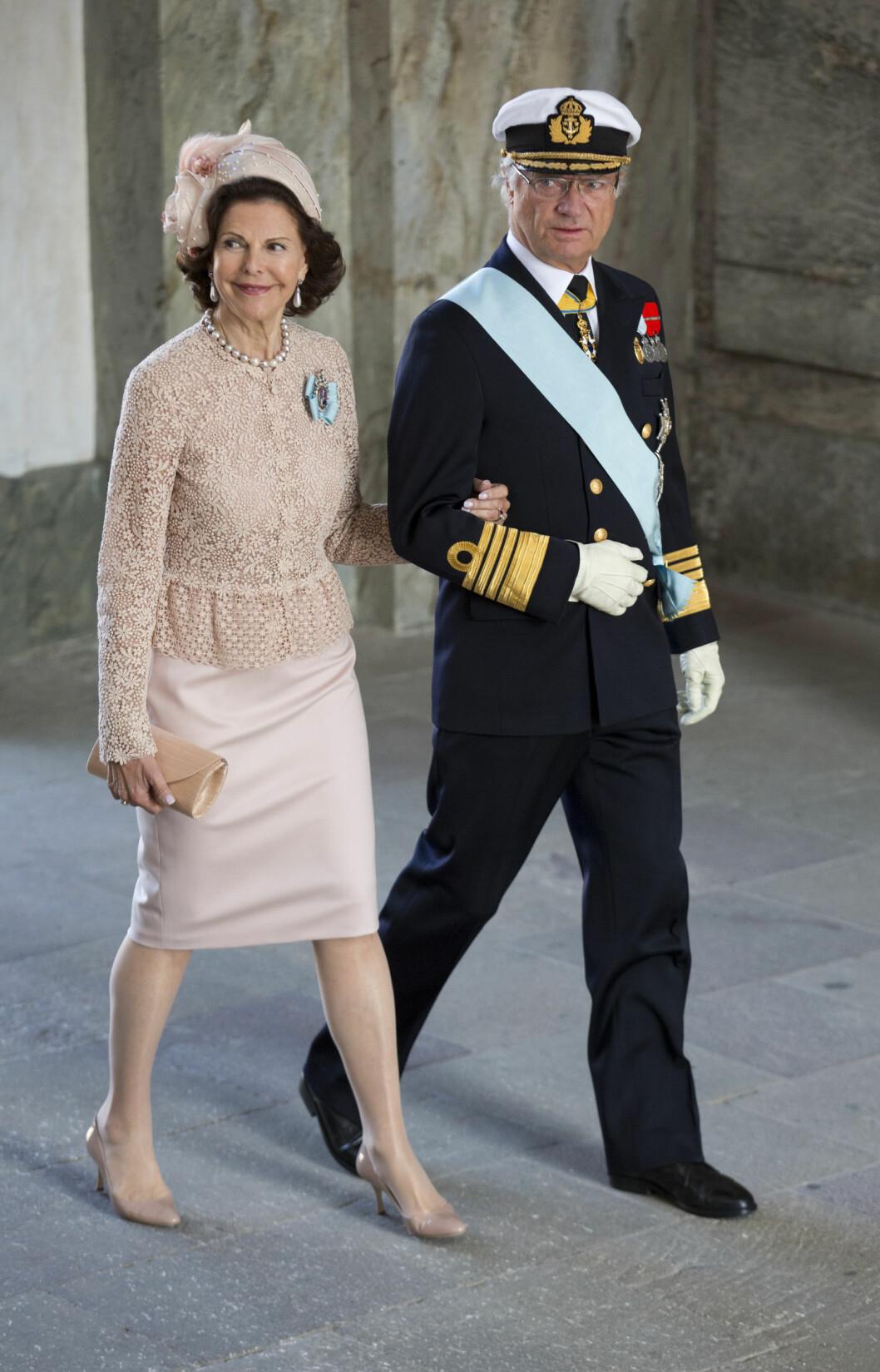 BORTREIST: Dronning Silvia var ikke i Stockholm da sønnen ble pappa for første gang. Her er det svenske kongeparet sammen under dåpen til prinsesse Estelle for fire år siden. Foto: Julian Parker/UK Press Ltd