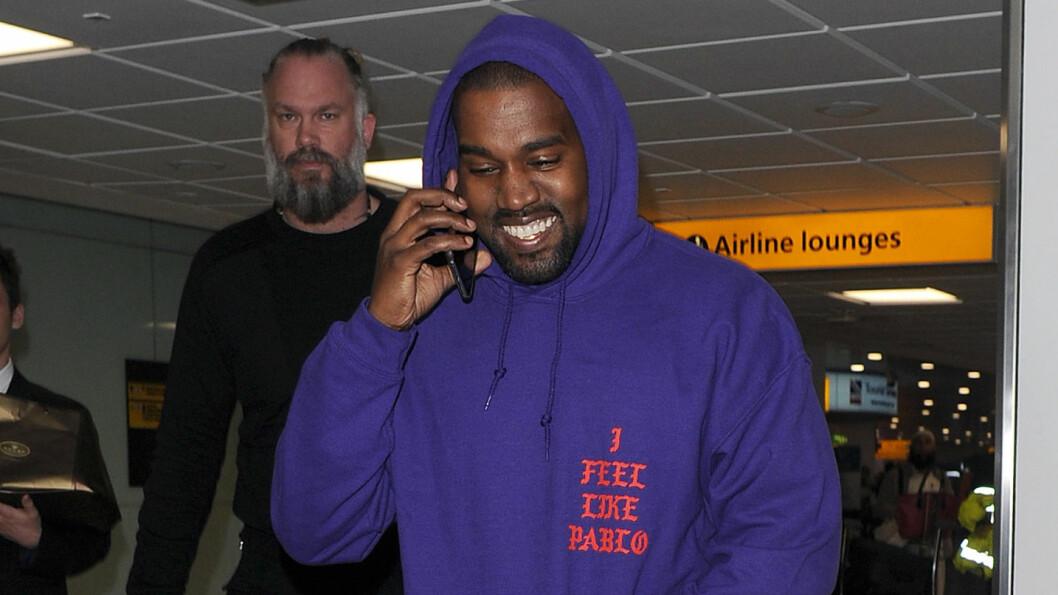 STORT SMIL: Kanye West var i godt humør da han landet på flyplassen Heathrow i London før han reiste videre til Skottland.  Foto: wenn.com
