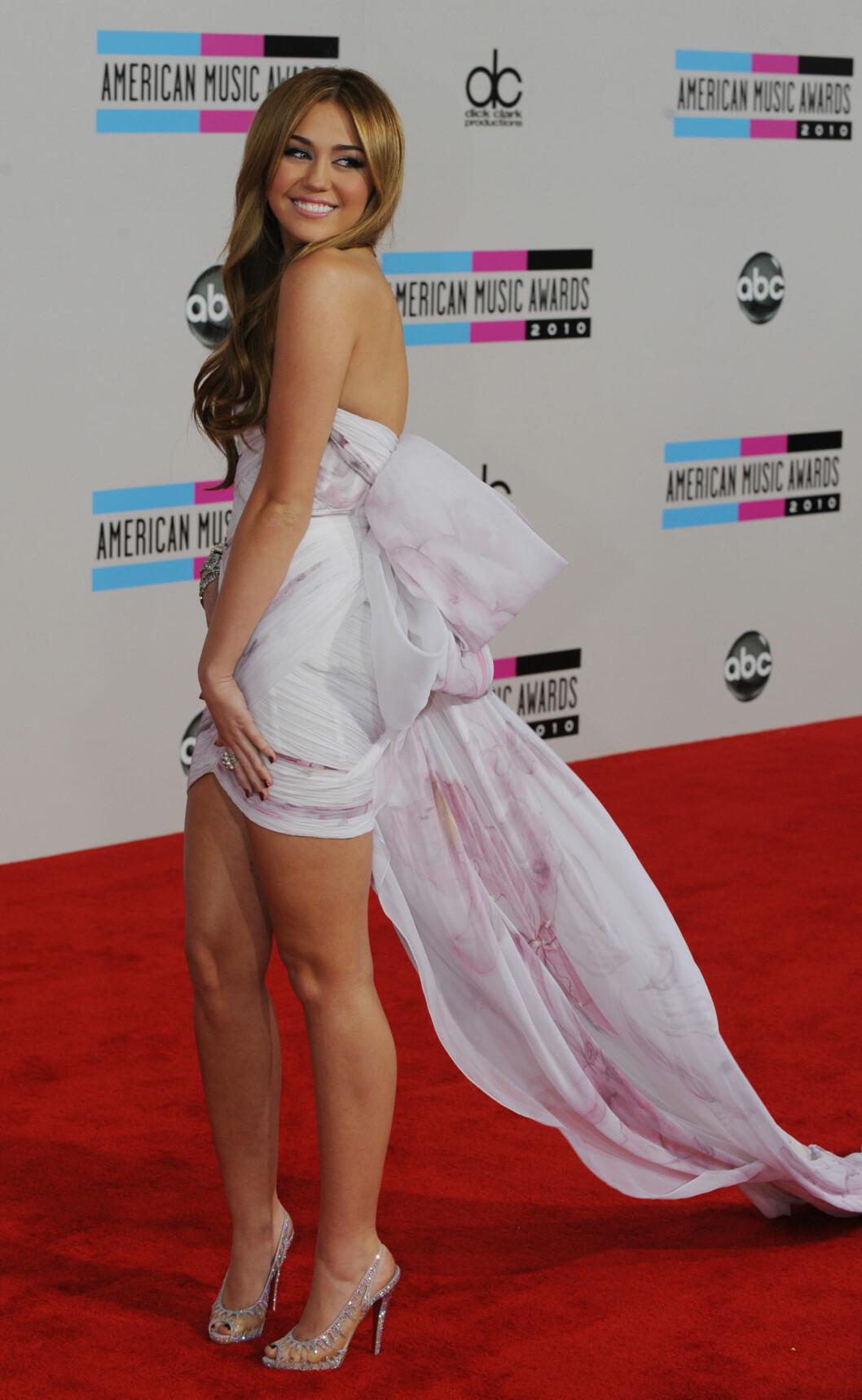 SPESIELT KJOLEVALG: Miley fikk mye oppmerksomhet da hun entret den rød løperen i denne flotte kreasjonen i 2010. Det var også dette året hun møtte sin tidligere forlovede Liam Hemsworth, under innspillingen av filmen «The Last Song». Foto: Afp