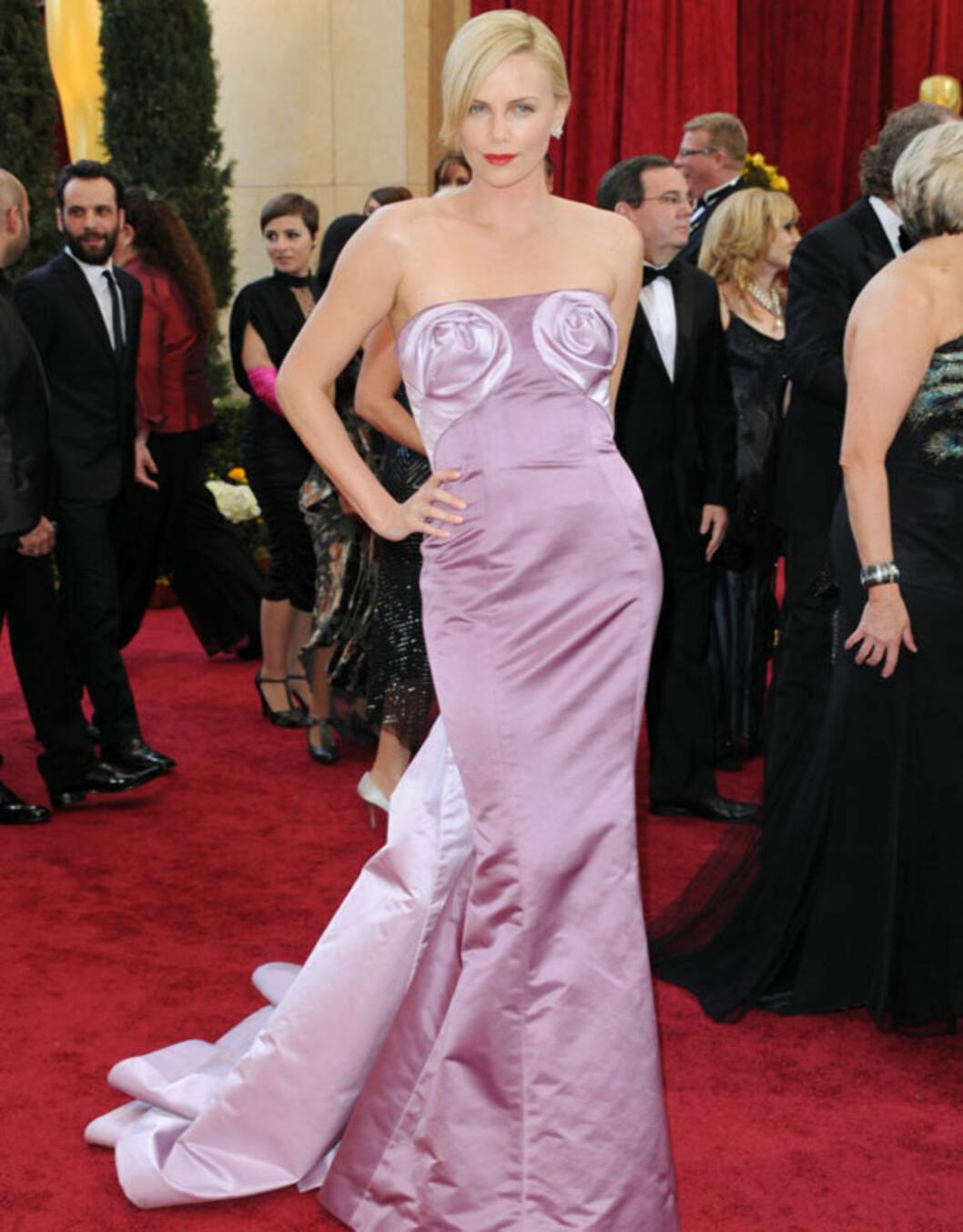FRODIG BYSTE: Charlize Therons Dior-kjole vakte oppsikt med de strategisk plasserte «blomstene» på utdelingen i 2010.  Moviefone skrev at de trakk all oppmerksomheten bort fra stjernens skjønnhet.  Foto: All Over Press