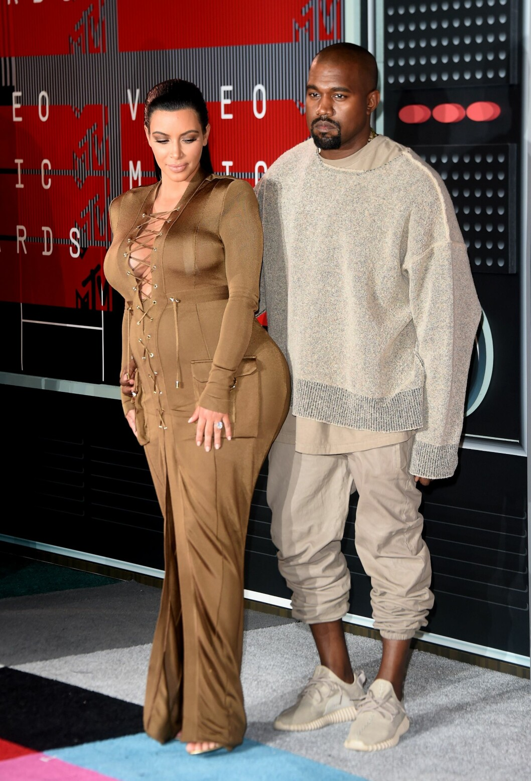 <strong>DOBBEL BOM:</strong> En annen overraskelse under MTV Video Music Awards var antrekkene til verdens mest berømte par: Kim Kardashian og Kanye West. Kim var gravid med sitt andre barn og viste mye former i en lang brun kjole med utringet snøre-topp fra Balmain. Rapperen fikk heller ikke skryt for sine halvlange bukser og grå oversized genser.  Foto: Afp