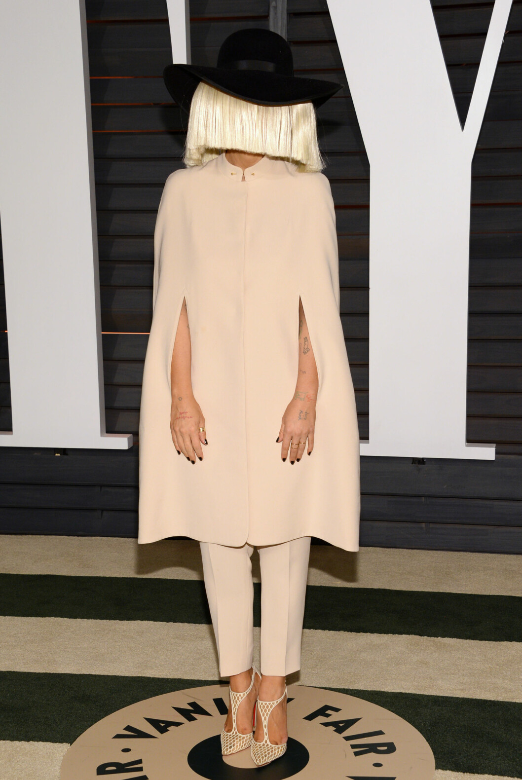 <strong>PEEKABO:</strong> Sangeren Sia skjulte ansiktet under en lang blond parykk under Vanity Fairs Oscar-fest i februar. Hun skjulte også kroppen i en beige kåpe, med beige bukser og beige sko på den beige løperen.  Foto: Ap