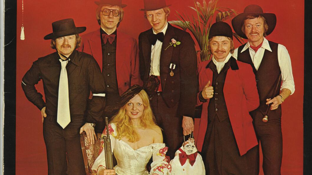 FLYNDRE OG MASKINGEVÆR: Legg merke til detaljene på dette albumet til gruppen Four Jets fra 1977 - en flyndre med påmalt ansikt, en mann i bunad og skøyter, og den smilende kvinnen med maskingevær av typen AG-3. Foto: VENDETTA FORLAG