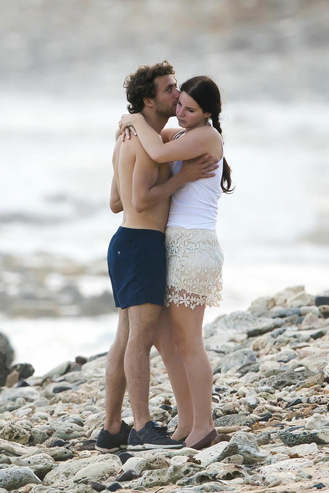 OMFAVNELSER: En noe mutt Lana Del Rey så ut til å bli muntret opp av Francesco Carrozzini på stranden. Foto: /All Over Press
