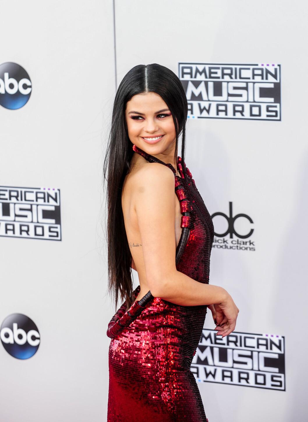 STRÅLTE: Selena Gomez var litt av et syn under søndagens prisutdeling i en rød kjole med utringet rygg fra Givenchy.  Foto: SipaUSA