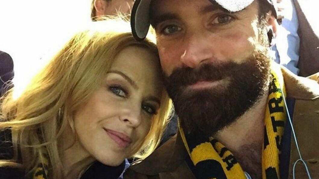 FORELSKET: Kylie Minogue har falt for den unge skuespilleren Joshua Sasse. Her er de sammen på en rugbykamp. Foto: Instagram/Joshua Sasse