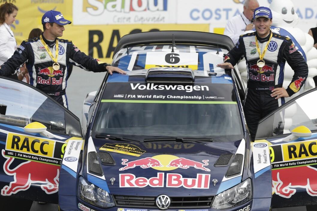 TALENTFULL: Andreas Mikkelsen (t.h) er den yngste sjåfør som har tatt WRC-poeng noensinne, og er tidligere landslagsutøver i alpint og motocross. Her med Ola Floene og deres Volkswagen Polo R WRC etter å ha vunnet det 51. Rally i Catalonia sist måned. Foto: NTB Scanpix
