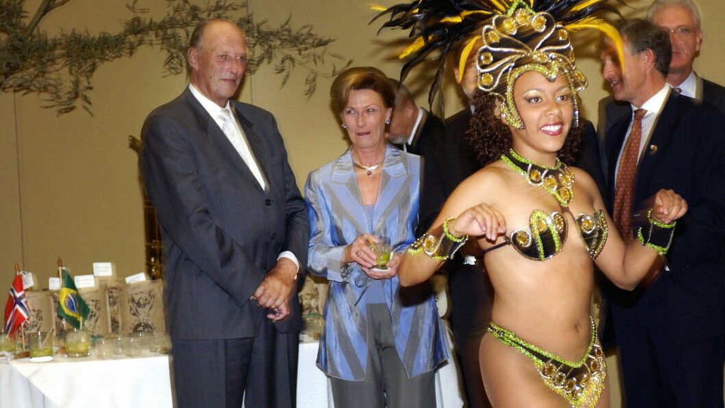 2003:  Dronning Sonja visste ikke helt hvor hun skulle feste øynene da to eksotiske samba-dansere underholdt under et kaffeseminar i Sao Paulo. Den ene forsøkte også forgjeves å få kong Harald med ut på dansegulvet, men han nøyde seg med å se på opptrinnet. Foto: NTB scanpix
