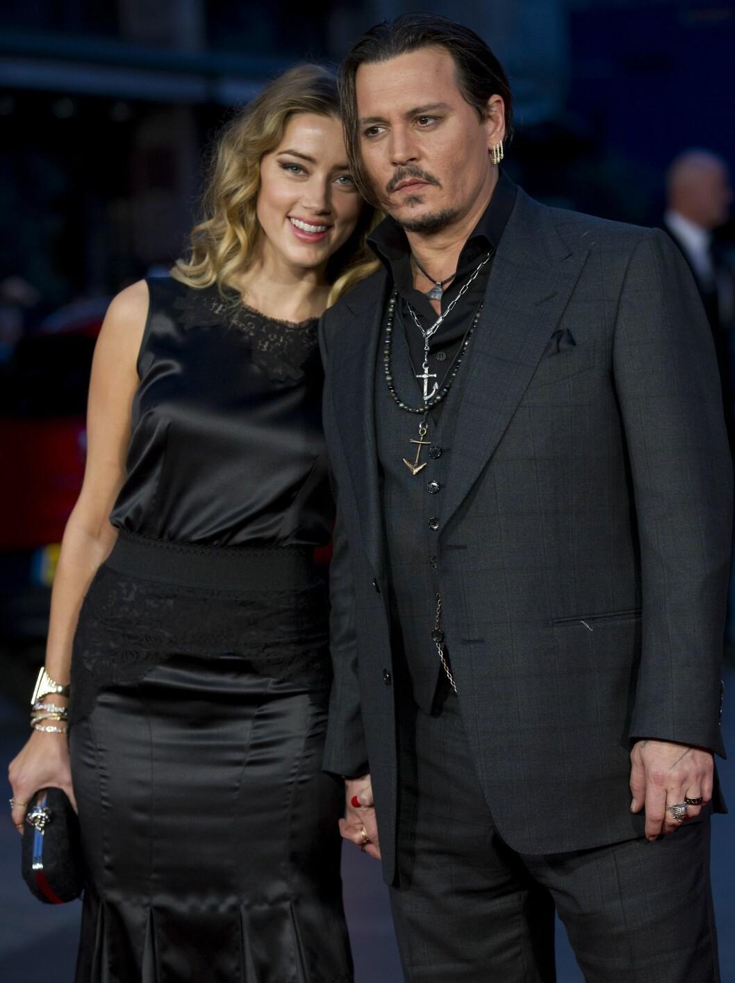 BENEKTER BRUDD: Ryktene om et brudd har sirkulert rundt paret den siste måneden, men Amber og Johnny viser seg stadig hånd i hånd på filmpremierer.  Foto: Afp